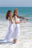 Two young female violinists on beach — Stock Photo