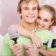 Happy young couple painting new home — Stock Photo