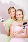 Young couple painting new home wall together — Stock Photo