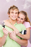 Young happy couple painting new home — Stock Photo