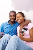 Happy african couple painting new home — Stock Photo