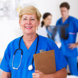 Happy female senior nurse and colleagues in hospital ward — Stock Photo