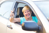 Happy female senior driver holding car key — Stock Photo