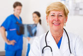 Happy female senior medical worker and staff in hospital ward — Stock Photo