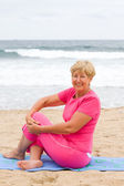 Happy senior woman doing fitness on beach — Stock Photo