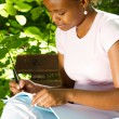 Stock Photo: Female african american student studying outdoors