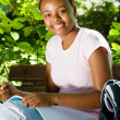 Happy female african american student studying outdoors — Stock Photo