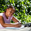Female african college student studying outdoors - Stock Photo