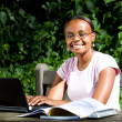 Female african college student using laptop outdoors — Stock Photo