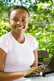 Female african american high school student using laptop outdoors — Stock Photo