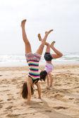 Twee tiener meisjes doen handstand op strand — Stockfoto