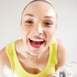Laughing young woman with paintbrush and roller — Stock Photo #16769603