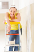 Happy young woman standing on ladder with painting roller — Stock Photo