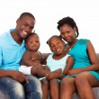 Foto Stock: Happy african american family sitting on sofa