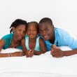 Happy african american family lying on bed — Stock Photo
