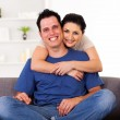 Young loving couple hugging on sofa at home — Stock Photo