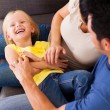 Parents tickling little daughter on sofa — Stock Photo