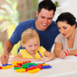 Happy parents watching little daughter drawing picture — Stock Photo
