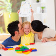Happy parents kissing cute little daughter with her drawing — Stock Photo