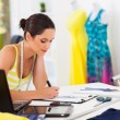 Pretty female fashion designer drawing new designs — Stock Photo #18714453