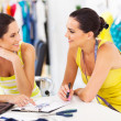 Two happy fashion designers discussing new design in studio - Stock Photo