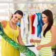 Happy fashion designer showing a dress to her customer — Stock Photo