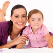 Cute mother and little daughter on bed — Stock Photo #18714769
