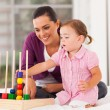 Little girl playing educational toy with mother on bed - Foto Stock