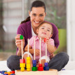 Happy little girl playing wooden toy with mother at home — Stock Photo