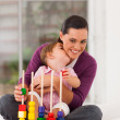Cute daughter kissing mother while playing with toy — Stock Photo