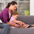 Mother teaching daughter drawing on sofa at home — Stock Photo