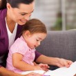 Mother teaching little daughter drawing at home — Stock Photo #18714935