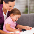 Mother teaching little daughter drawing at home — Photo