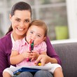 Stock Photo: Happy mother and little daughter with crayon at home