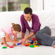 Happy mother and daughter playing with toy on bedroom floor — Stock Photo #18714999
