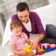 Loving mother and daughter playing with toy at home — Stock Photo