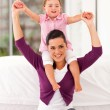 Happy little girl sitting on mother's shoulders at home — Stock Photo #18715053