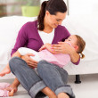 Stock Photo: Caring mother rocking her baby girl to sleep