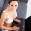 Pretty young woman in underwear using laptop on sofa — Stock Photo