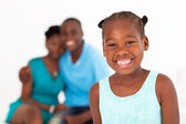 Happy african american little girl standing in front of parents — Stock Photo