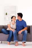 Young couple sitting on sofa at home — Stock Photo