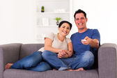 Young couple watching comedy at home — Stock Photo