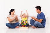 Happy little girl playing toys with parents on bedroom floor — Stok fotoğraf
