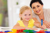 Cute little girl drawing with mother at home — Stok fotoğraf
