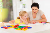 Mother teaching little daughter drawing at home — Stockfoto