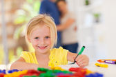 Happy little girl drawing in front of parents at home — Stock Photo