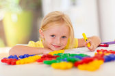 Cute little girl drawing with crayon at home — Stock Photo