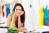 Attractive young female dressmaker sketching in studio — Stock Photo