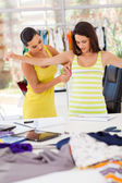 Female dressmaker measuring client's bust size — Stock Photo