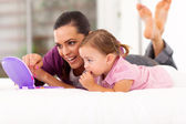 Happy mother and daughter playing with toy laptop on bed — Stock Photo